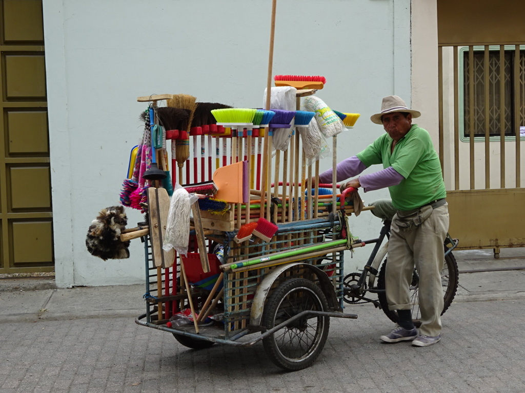 Selling brooms from a bicycle has got to be a hard way to make a living!