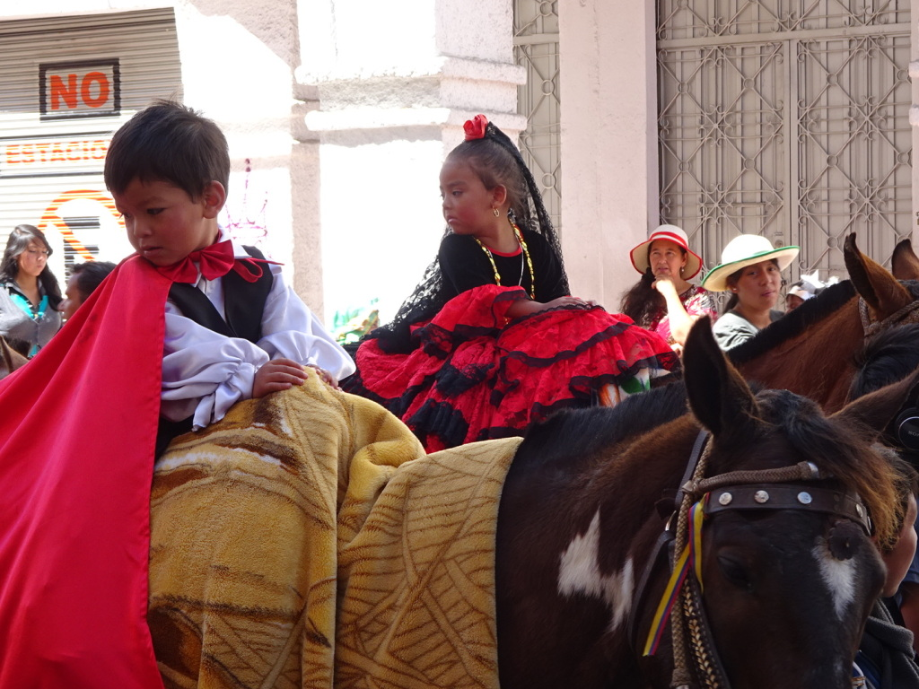 There were many horses topped with little children in traditional costume. The dresses and capes cover the entire horse!