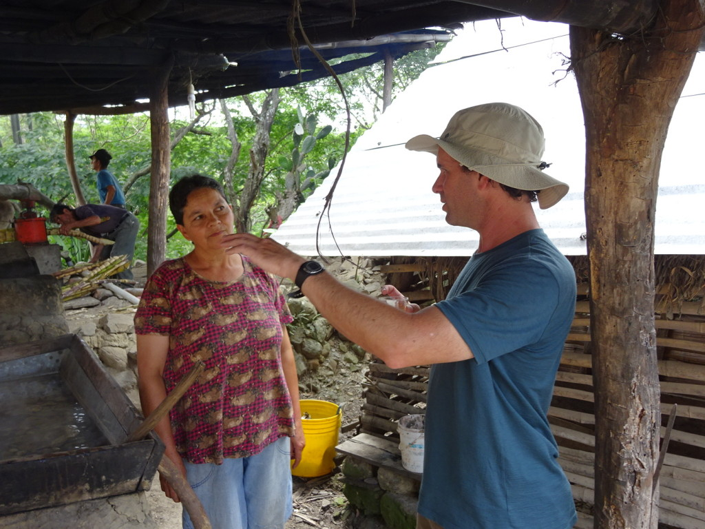 Talking with one of the brother's wives. She cooks down the juice from the sugar cane.