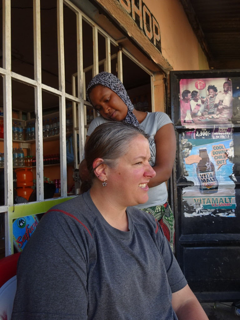 Our friend Vicky gives me a new fancy braid/bun infront of Ruth Place. That's where I learned beauty does has a price.