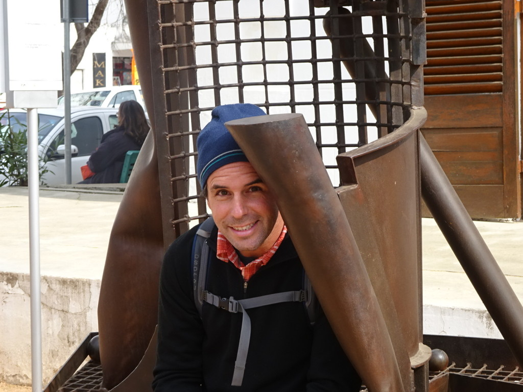 Aaron sitting in a weird but cool sculpture.