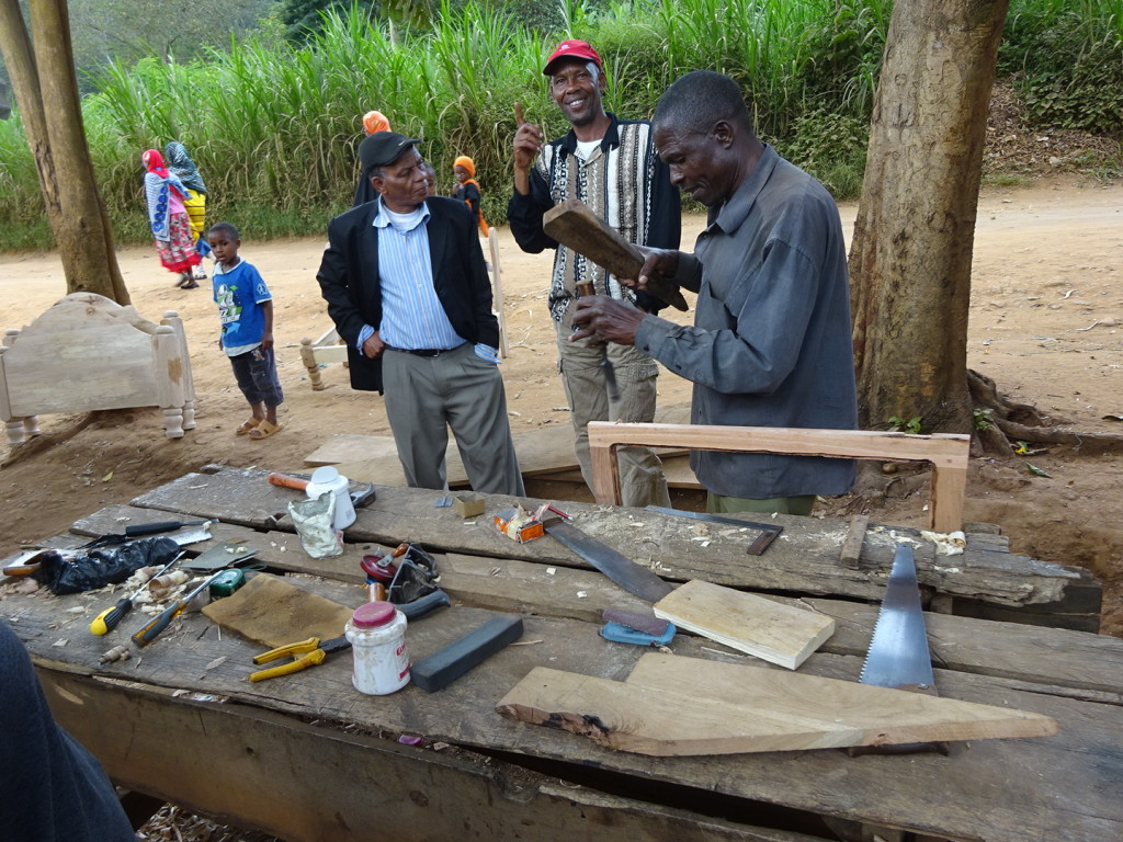 Cutting the hinge spots for a door frame in Tanzania - all you need is a piece of wood and something to use for a chisel.