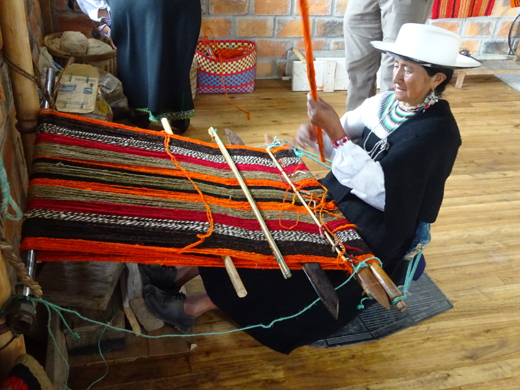 Abellina at the seated loom. She has a rough wood support behind her lower back which pulls the loom taut when she leans back. If you're curious, this is being woven with both natural and synthetic dyed wools.