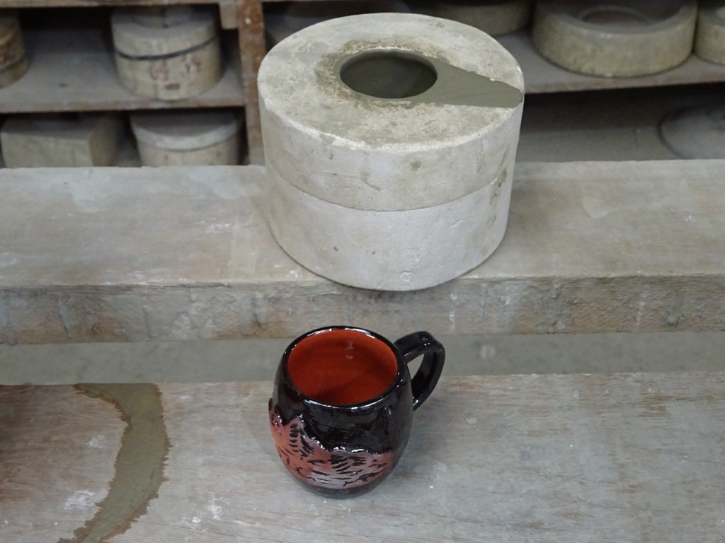 ...then he pours out the slip so that he has a hollow mug form inside the mold!