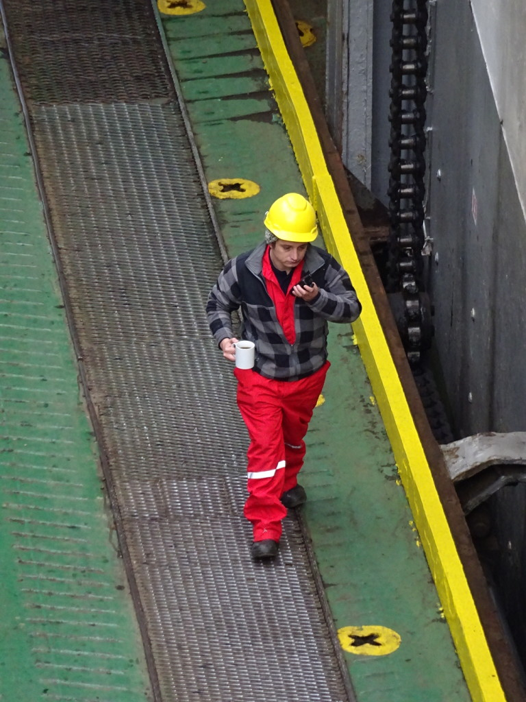 Worker helping load the vessel...and as any good Seattleite can tell you... you need a cuppa coffee to do a job right.