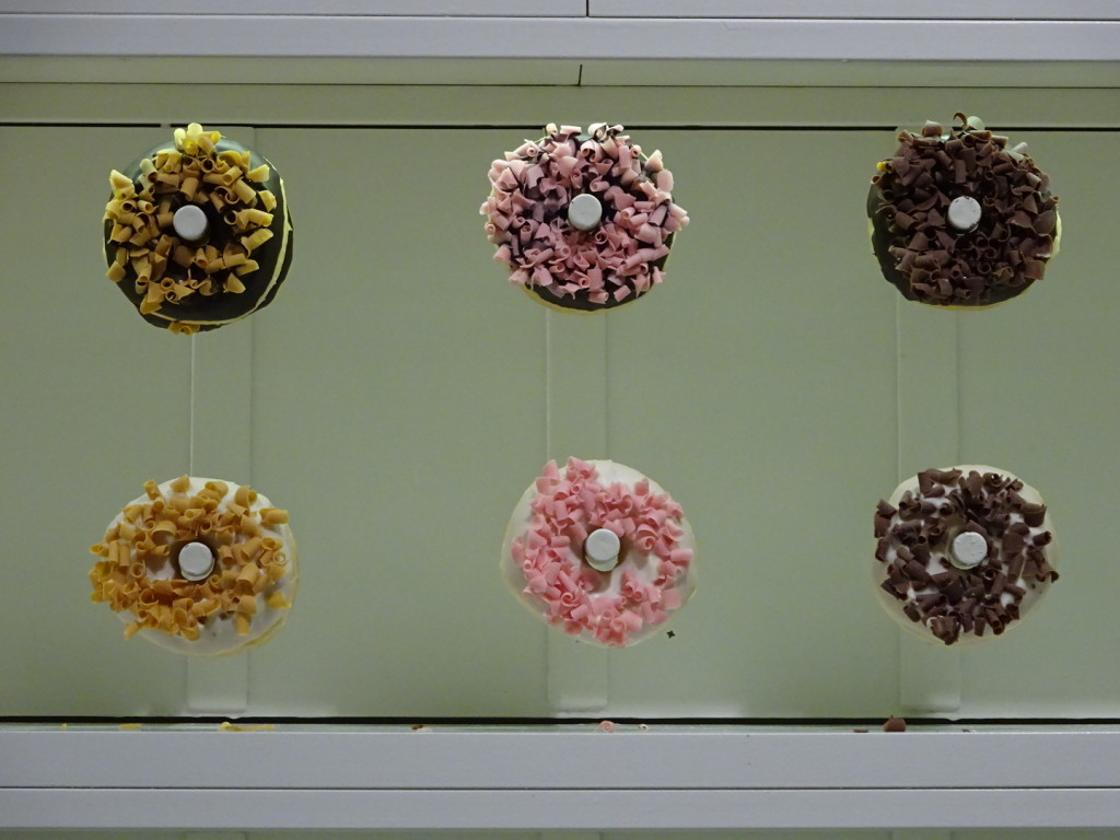 There is an entire wall behind the register with fancy donuts on pegs. They reflect in a wall sized mirror where the queue forms.